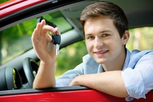 Jugendlicher mit neuem Auto und Fahrzeugschlüssel