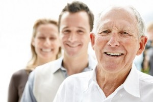 Closeup portrait of an old man smiling with his son and daughter in background against bright background