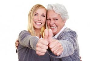 Lachende Oma und ihre Enkeltochter halten Daumen hoch
