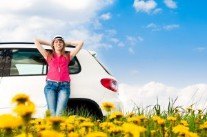 Beautiful young woman resting at side of her car at flower field with blue cloudy sky in background